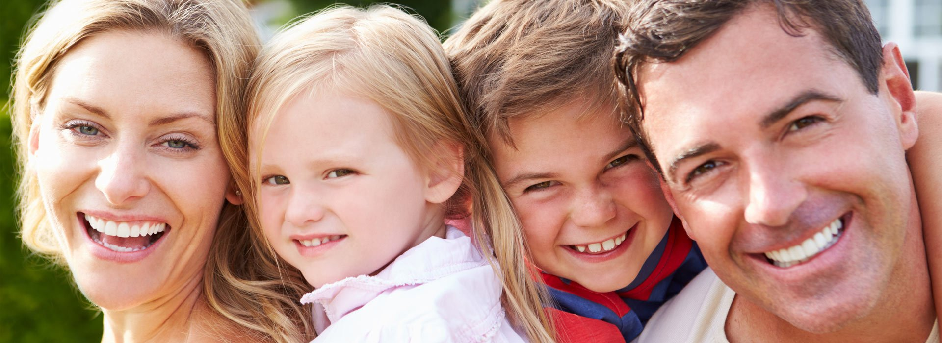 family smiling outside