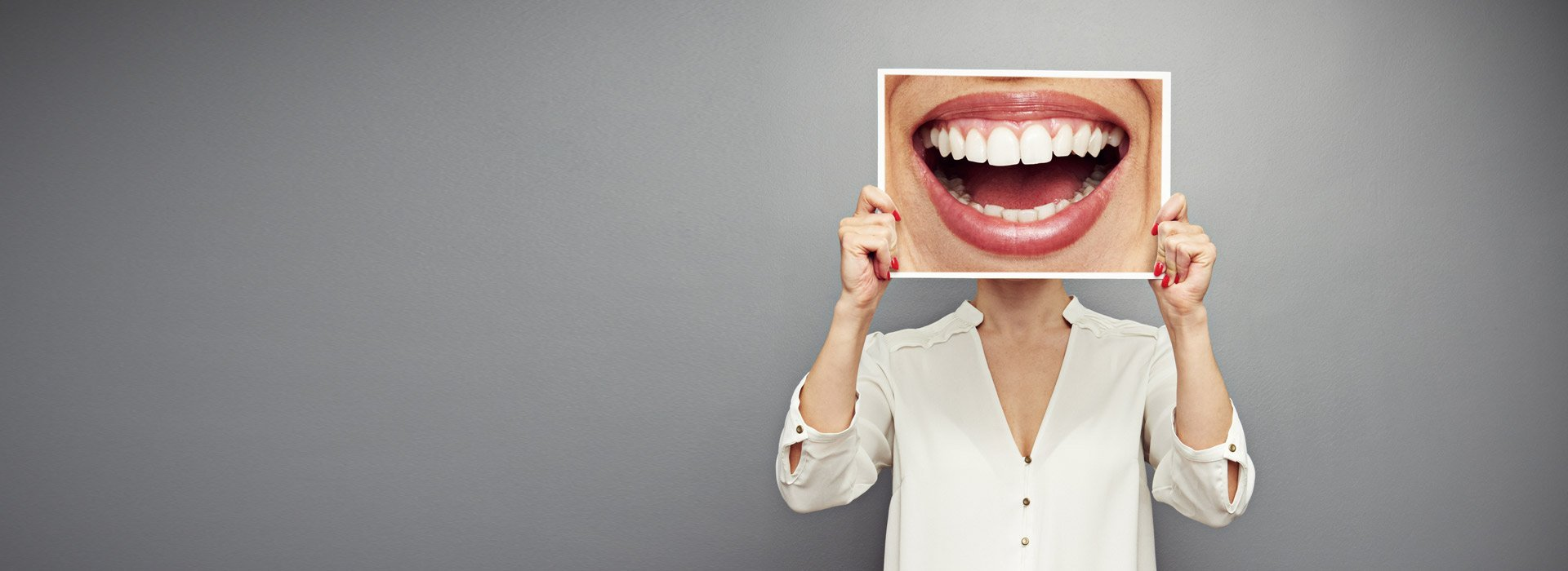 woman holding up a enlarge mouth smiling picture