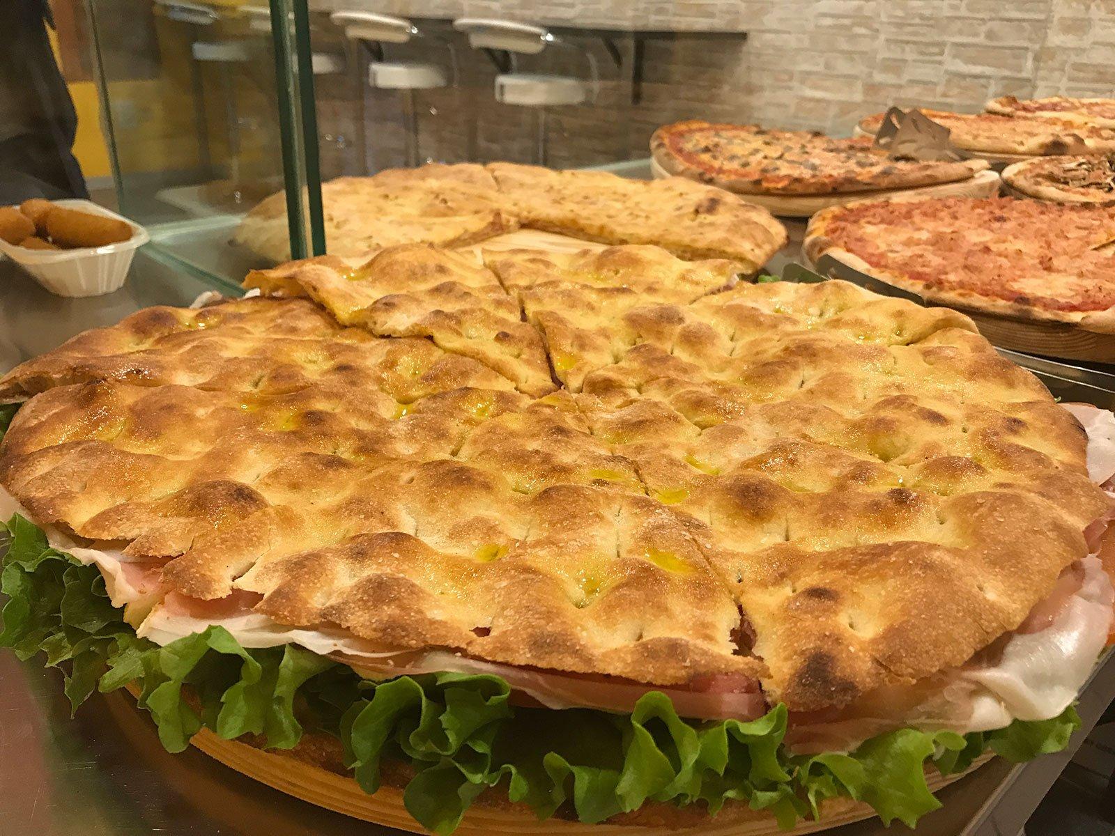 un enorme sandwich di pizza farcito