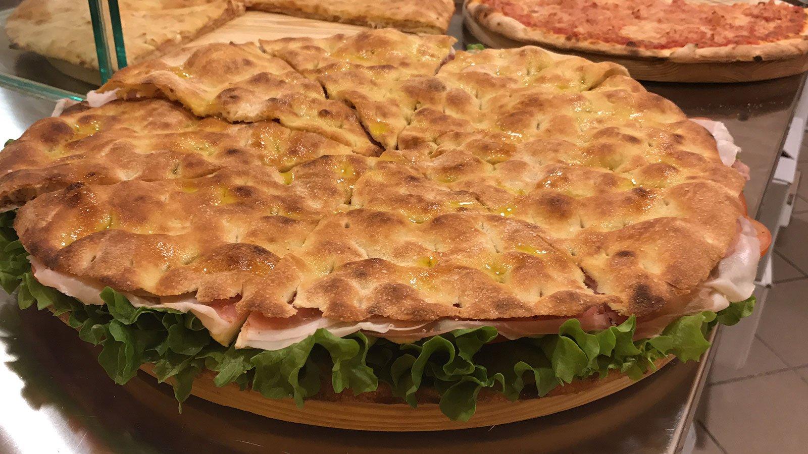 un enorme sandwich di pizza farcito su un tagliere