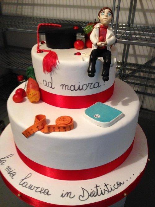 una torta a tre piani con un pupazzetto e un cappellino da laurea