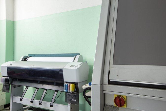 vista di una stampante da tipografia con cartucce di inchiostro a vista e accanto un altra macchina