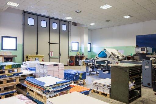 all'interno della tipografia dei bancali con delle confezioni di carta di diverse dimensioni e dei macchinari
