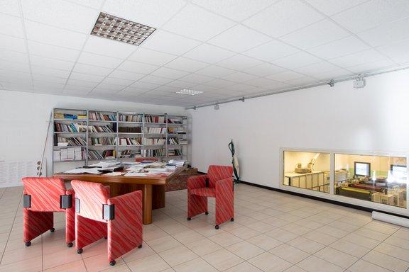 un ufficio ampio con una scrivania in legno, delle poltroncine rosse, una libreria e sulla destra una vetrata e dall'altra parte dei  monitor con delle macchine da strampa