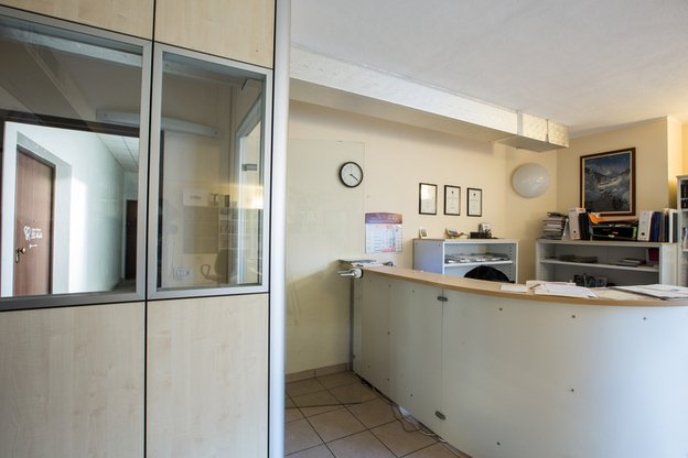 stanza con sulla destra una scrivania angolare alta di color bianco stile reception e sulla sinistra una cabina che porta a un corridoio con una porta