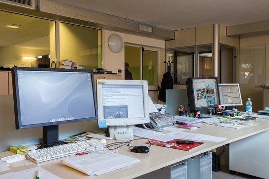 una scrivania con sopra dei fogli e 4 monitor, dietro si vede un appendino con un giubbotto appeso e vetri da cui si vedono altri uffici