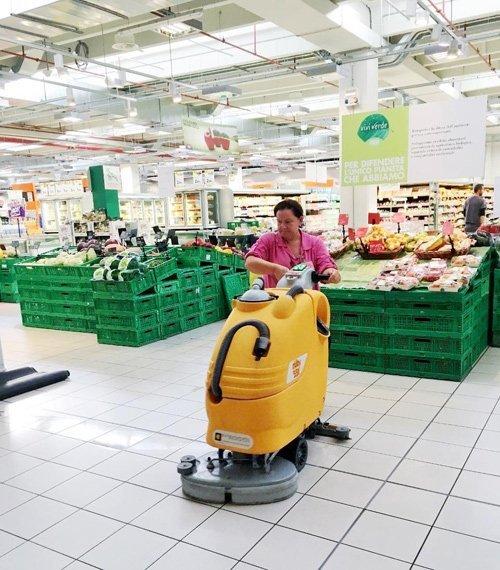 donna lucida il pavimento di un supermercato