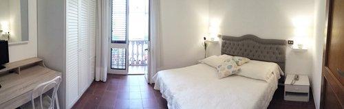 camera di albergo con letto bianco e balcone