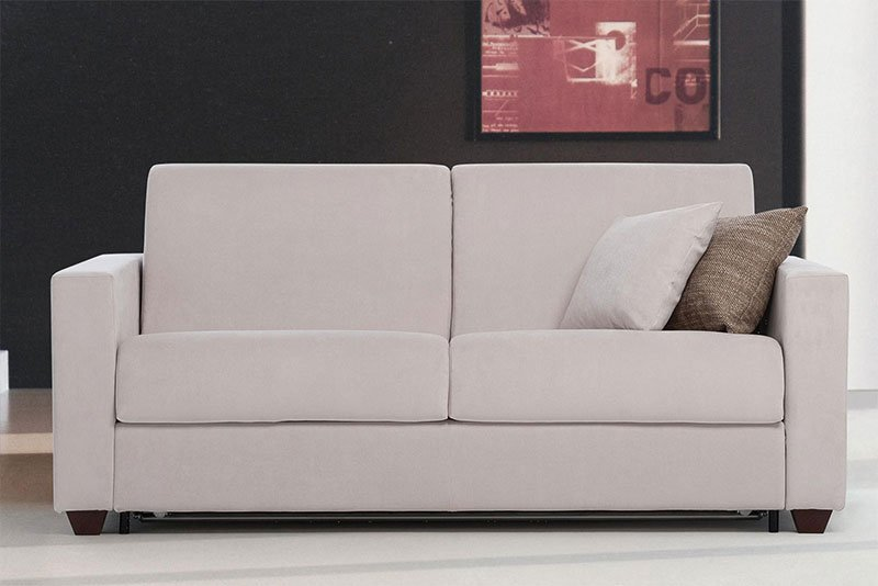 un divano a due posti color panna e dei cuscini colorati