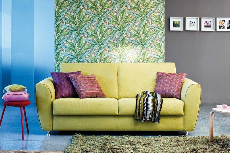 un divano giallo a due posti con dei cuscini viola e una sciarpa di lana