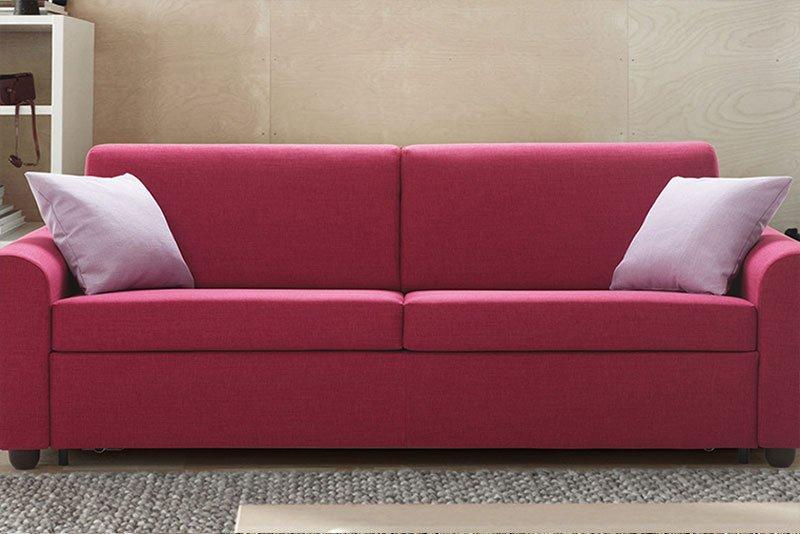 un divano fucsia a due posti con dei cuscini