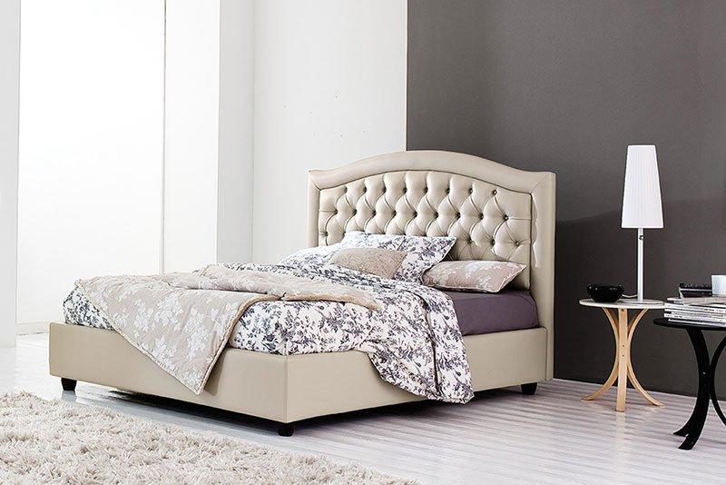 un letto color beige chiaro con testata imbottita