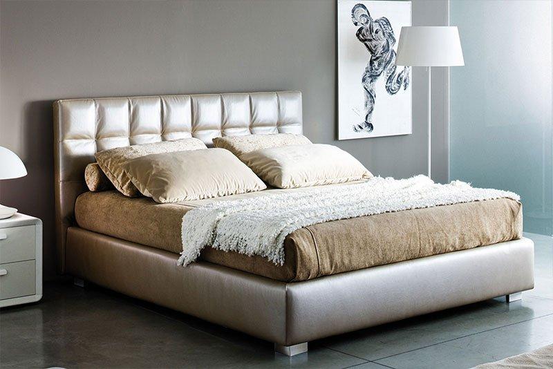 un letto con testata imbottita di color oro