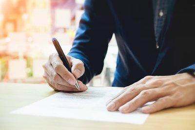 uomo in giacca scrive su un documento