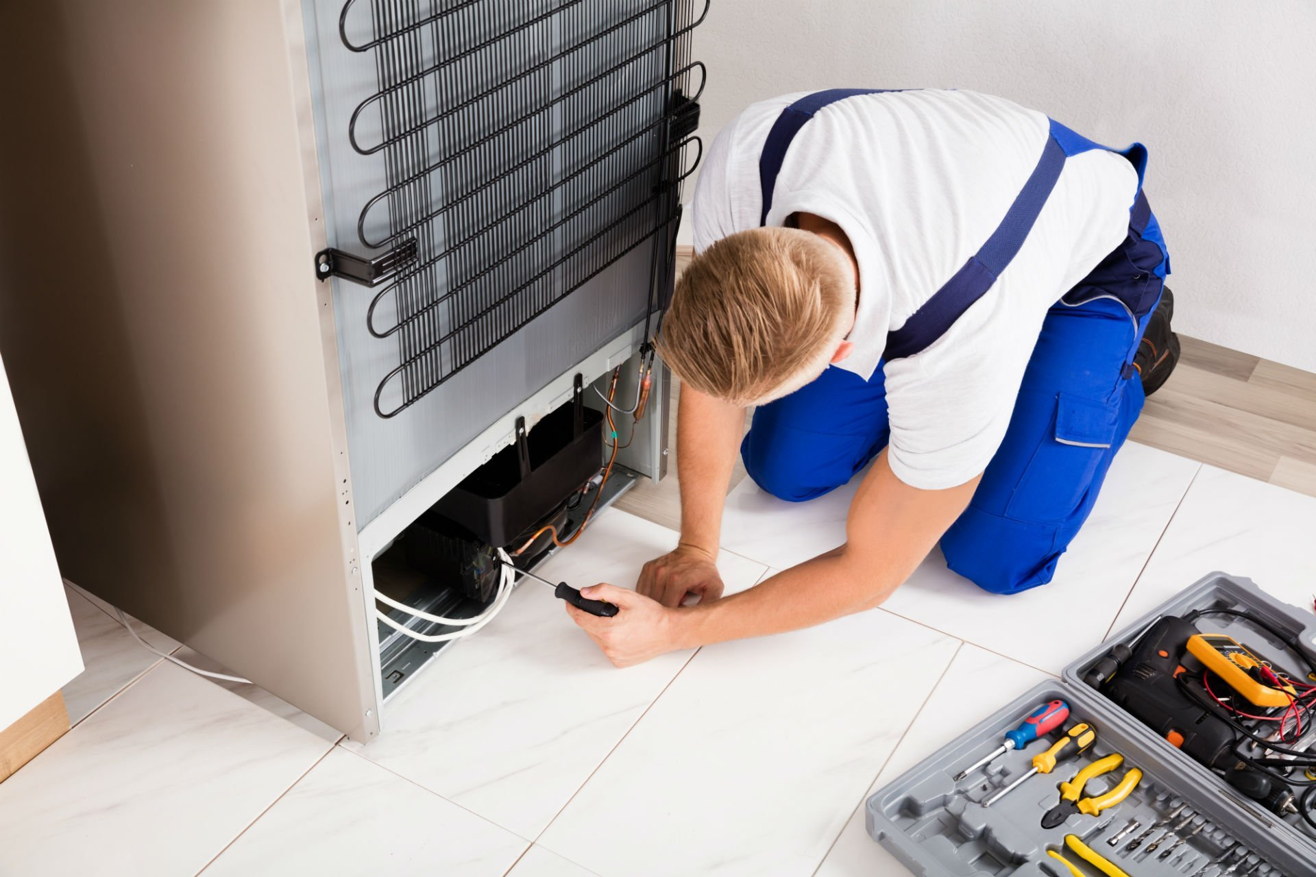un tecnico che sistema un frigorifero