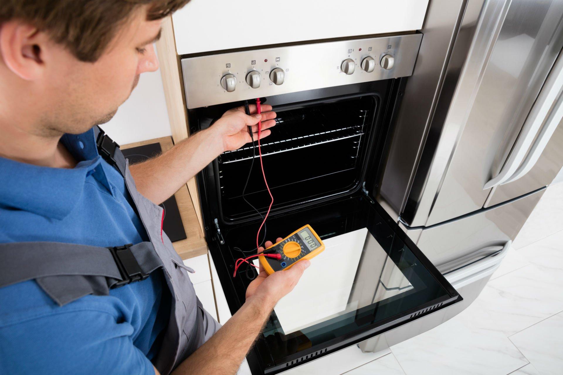 un tecnico con un tester che testa un forno