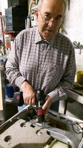 un signore con un trapano in mano durante una riparazione