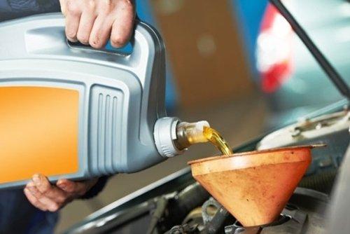 persona che versa benzina in un imbuto con cruscotto aperto auto