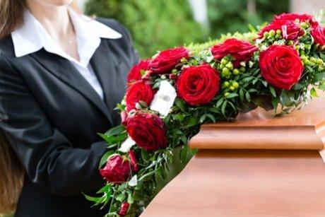 rose rosse su un cofano funebre