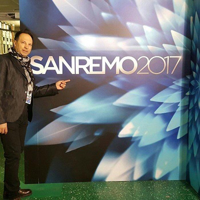 Proprietario del Parrucchiere Uomo - Donna Stile e Moda di fronte al cartellone di Sanremo 2017