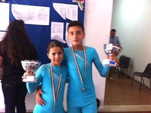 due giovani pattinatori con trofeo e medaglie