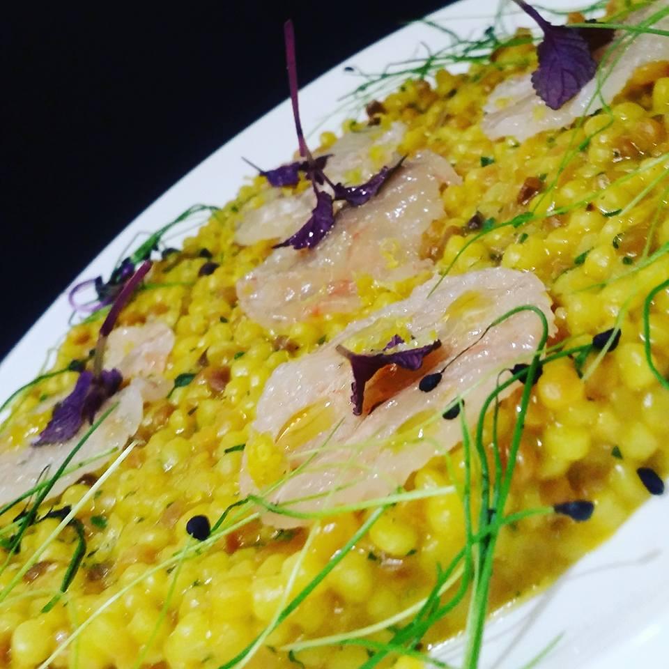 Un risotto con carpaccio di pesce ben impiattato