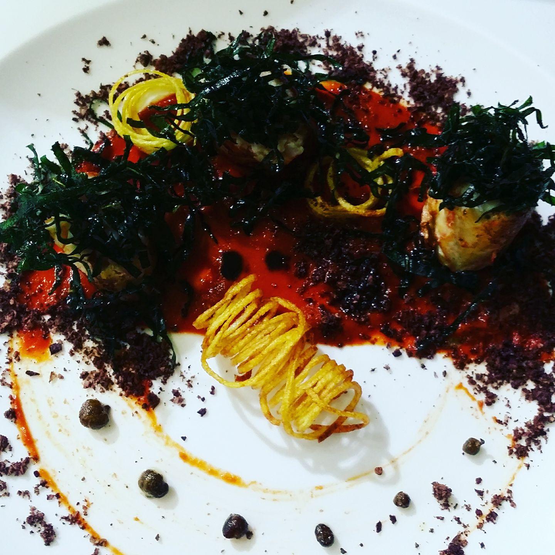 Del pesce in un piatto decorato con erbe, spaghetto fritto e verdure