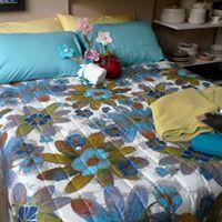 letto matrimonial con fiori appoggiati sui cuscini