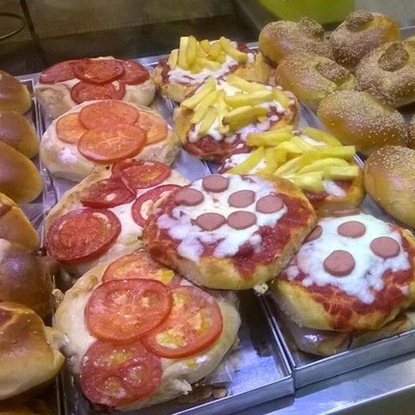 delle pizzette con patatine, salame e pomodorini