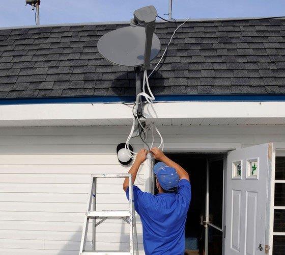 A man installing a Sky dish