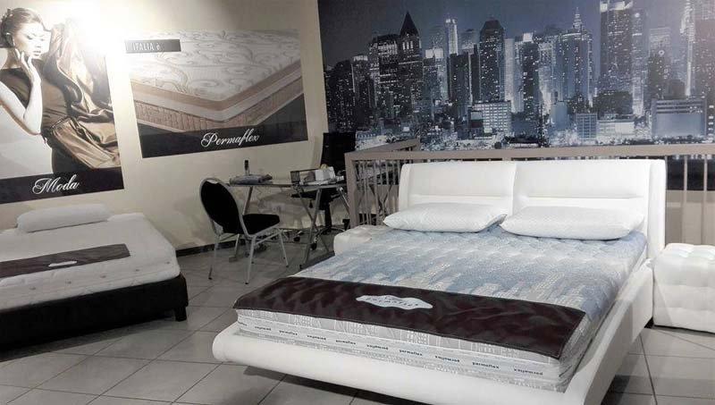 Un letto matrimoniale bianco e un quadro di grattacieli esposti in un negozio