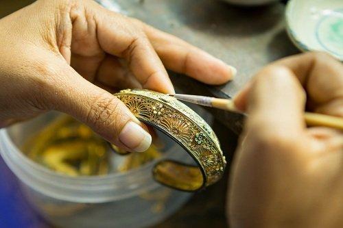 oreficie lavora in un braccialetto di oro e pietre preziose
