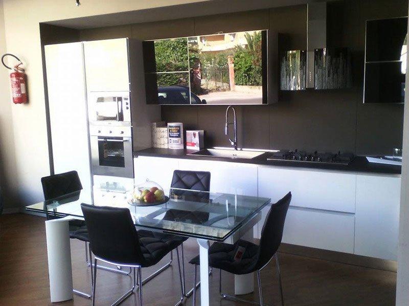 Moderna cucina integrata in legno e acciaio,la tavola di vetro le dà un tocco diverso