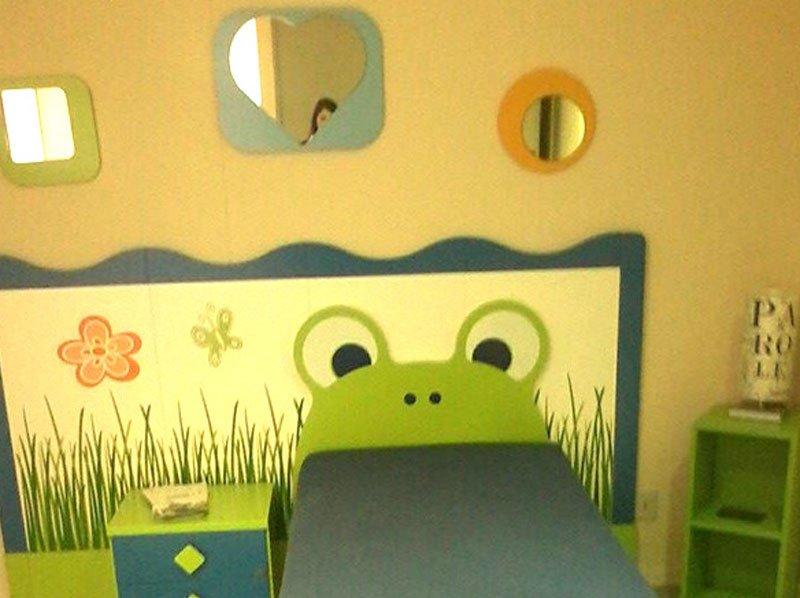 Simpatico quarto infantile, il letto è la lingua della rana ,specchi con differenti forme e colori e i mobili in verde per far gioco con il paesaggio del corpo del letto