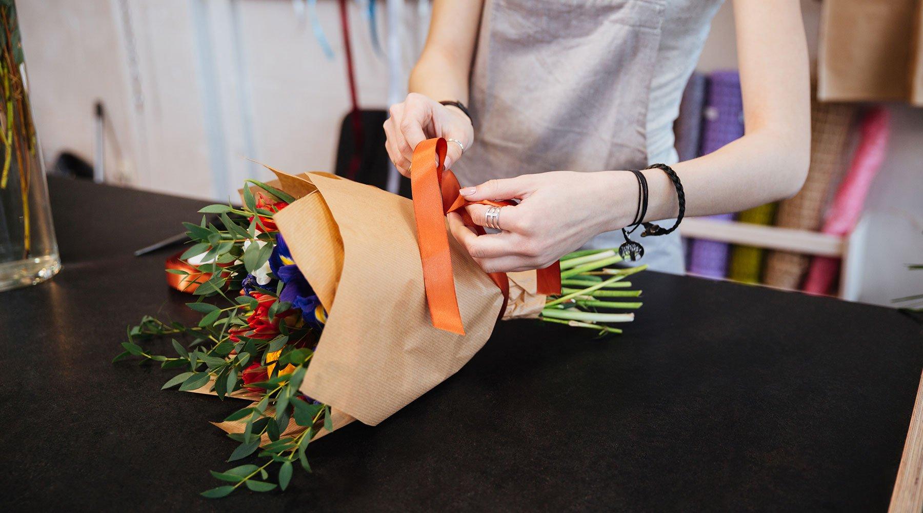 Una fiorista mentre lega un fiocco arancione su un mazzo di fiori di colore blu e rosso, messi sul piano di lavoro nero