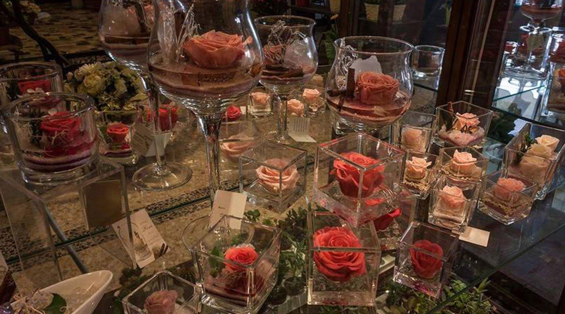 Mensole con Rose di vari colori all'interno di bicchieri di vino dalle forme rotonde e quadrate
