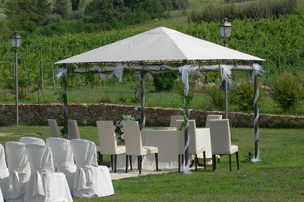 Gazebo decorato con velo bianco nel verde, vista colline, sedie coperte e copri sedie bianche con fiocco