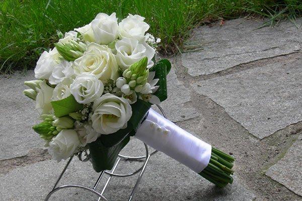 Bouquet di fiori bianchi legati con un nastro satinato, appoggiati su struttura di metallo