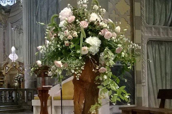 Interno della chiesa,Grande composizione di fiori rosa e bianchi nel centro, candele bianchi intorno sui tronchi di legno