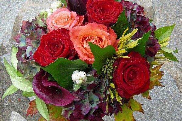 Rose rosse, arancioni, vite di canada, foglie di vari colori, messi in una fioriera di acciaio