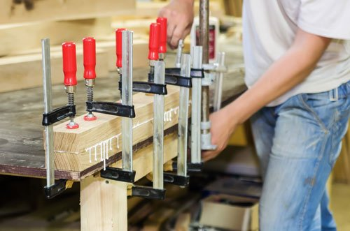 un operaio e accanto delle assi di legno con dei morsetti