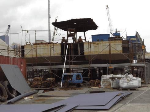 un cantiere con dei tubi di ferro da fondamenta,un impalcatura e degli operai al lavoro