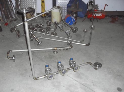 dei tubi con delle valvole, un compressore rosso e altro materiale