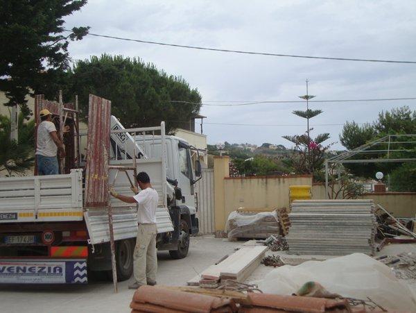 due operai caricano materiali edile su un mezzo