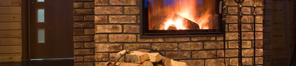 Logs burning in a stove set into a brick wall