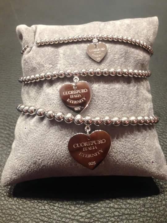 Un cuscino beige con impilati bracciali di metallo con placchette a forma di cuore