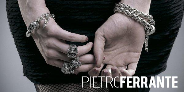 Due mani che si toccano, quella di sinistra indossa anelli e quella di destra un bracciale