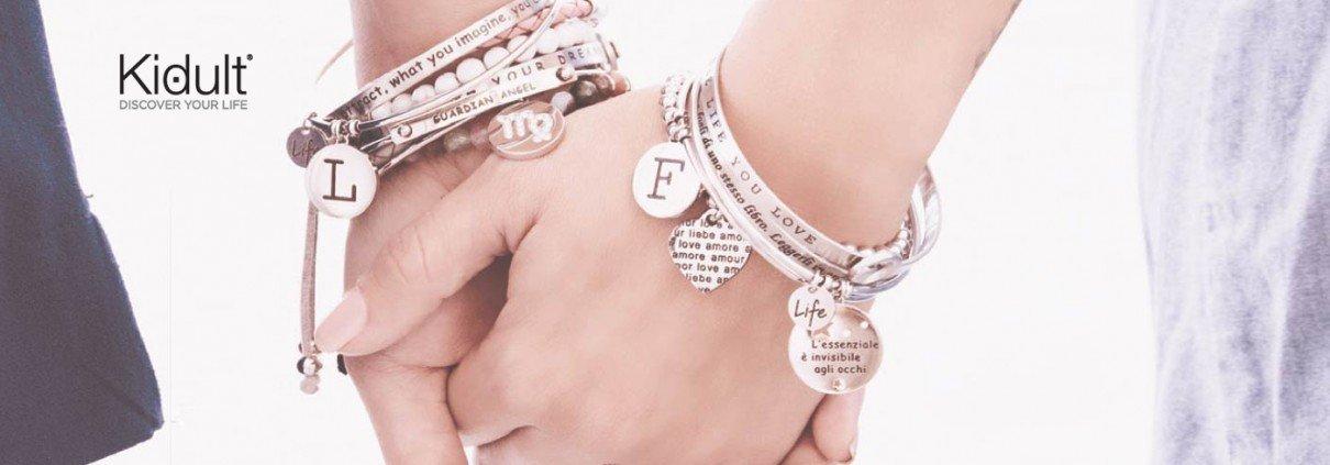 Due mani che si stringono, che indossano braccialetti di acciaio con placchette
