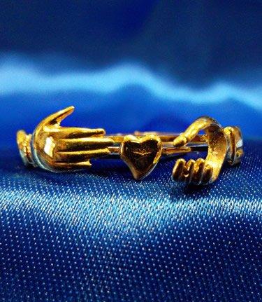 Braccialein acciaio dorato con decorazioni di mani e cuori