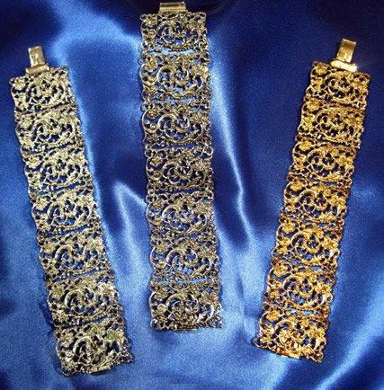 Tre gioielli di metallo dorato di forma rettangolare